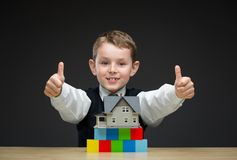 Thumbing up little boy with home model and blocks Royalty Free Stock Photos