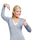 Thumbing up woman keeps key. Thumbing up woman in gray sweater keeps a key, isolated on white Royalty Free Stock Image