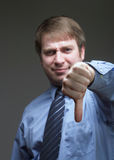 Thumbs down. Young businessman thumbs down gesture on dark background Stock Photos
