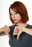 Thumbs Down. Young redhead woman pouts as she gives the thumbs down sign Royalty Free Stock Photography