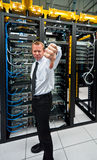 Thumbs down. Man posing a thumbs-down in front of data center server racks Stock Photography
