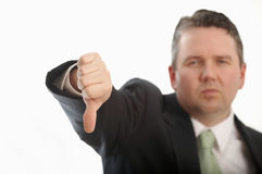 Thumbs down. Man in suit giving thumbs down, DOF focus on hand Royalty Free Stock Images