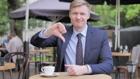 Thumbs Down by Businessman Sitting in Outdoor Cafe stock video