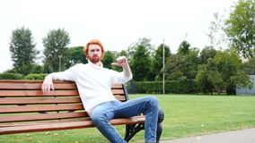 Thumbs Down by Man Sitting on Bench in Park, Red Hairs and Beard. 4k , high quality stock video