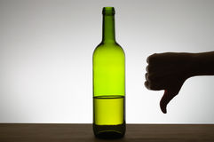 Thumbs down sign and a bottle of wine Royalty Free Stock Photos