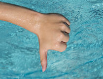 Thumbs down sign of young man, teenager with blue water as backg. Thumbs down sign of young man with wet hand, teenager with blue water as background Royalty Free Stock Images