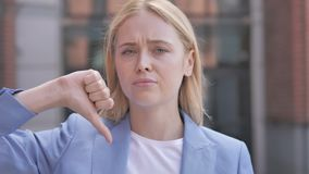 Thumbs down by young businesswoman, outdoor stock video footage