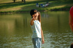 Thumbs up!!. Silly girl having fun at the park with her family Royalty Free Stock Images