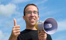 Thumbs Up. A young man holding a megaphone giving a thumbs up signal, with blue sky and clouds behind him Royalty Free Stock Image