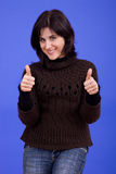 Thumbs up. Young beautiful woman, on a blue background Royalty Free Stock Images