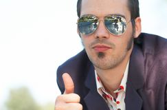 Thumbs Up. A young man in sunglasses gives the thumbs up indicating a done deal stock photos