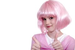 Thumbs Up!. Cute young girl in pink wig giving thumbs up signal isolated against a white backdrop Royalty Free Stock Photo