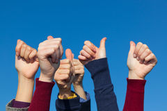 Thumbs Up. Multiracial Thumbs Up Against Blue Sky Stock Photos