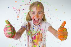 Thumbs Up. A young girl covered in paint giving the thumbs up in excitement Stock Image