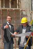Thumbs up. Two construction workers read paper Royalty Free Stock Image