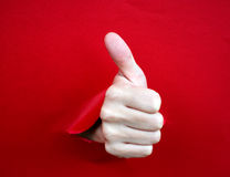 Thumbs up. Human hand with thumb up, coming out from a broken sheet of paper royalty free stock photos