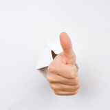 Thumbs up. Human hand with thumb up, coming out from a broken sheet of paper royalty free stock photo