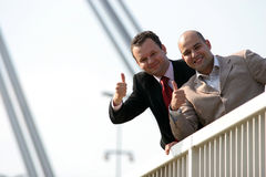 Thumbs up. Businessmen standing on bridge and holding thumbs up Stock Images
