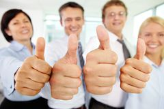 Thumbs up!. Cheerful business team holding their thumbs up with enthusiasm Royalty Free Stock Images