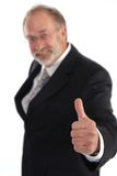 Thumbs Up. Senior businessman giving the thumbs up. Hand in focus Royalty Free Stock Photos