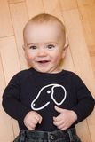 Thumbs up. Happy baby smiles and laughs while lying on floor giving thumbs up stock photo