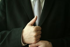Thumbs up. A business man gives the thumbs up royalty free stock image