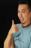 Thumbs up. Asian guy laughing and raise his thumb up Royalty Free Stock Images