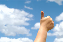 Thumbs up. Great blue sky luminating a thumbs up stock photo