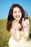 Thumbs up!. Beautiful young woman giving you a thumbs up and smiling in a field with a blue sky royalty free stock images
