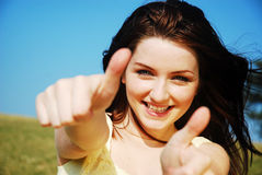 Thumbs up!. Beautiful young woman giving you a thumbs up and smiling in a field with a blue sky stock photography