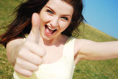 Thumbs up!. Beautiful young woman giving you a thumbs up and saying yeah royalty free stock photography