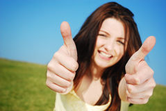 Thumbs up!. Beautiful young woman giving you a thumbs up and smiling in a field with a blue sky. Focus is on the hands royalty free stock image