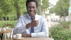 Thumbs Up by African Businessman Sitting in Outdoor Cafe stock footage