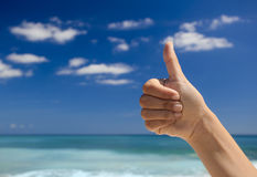 Thumbs up against a blue sky Royalty Free Stock Image