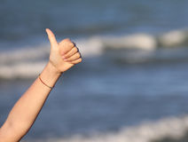 Thumbs up of baby's hand to say ok. And the background of the sea Stock Photos