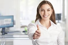 Thumbs up. A beautiful young businesswoman with toothy smile giving thumbs up while standing at the office stock photos