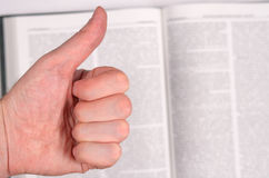Thumbs up and book. Stock Photos