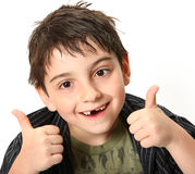 Thumbs Up boy. Silly seven year old boy making crossed eyes and thumbs up gesture Royalty Free Stock Images