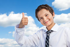 Thumbs Up. Boy in white shirt and a tie giving a thumbs-up. He is outside, with background a beautiful blue sky and white clouds Stock Photography