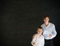 Thumbs up business man and boy on blackboard background Stock Photo