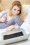 Thumbs up: closeup portrait of beautiful blond young business woman or student having fun working from home on laptop computer Stock Images