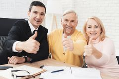 Thumbs up. A couple of old people at a reception with a realtor. They are satisfied with the service. Royalty Free Stock Photo
