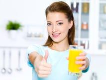 Thumbs-up da mulher com sumo de laranja Imagens de Stock Royalty Free