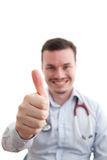 Thumbs up with depth of field. Thumbs up being given by a doctor who is out of focus Royalty Free Stock Photos