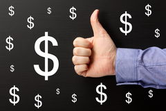 Thumbs Up for Dollars. Male hand wearing a business shirt giving the Thumbs Up sign for dollar signs on a blackboard Royalty Free Stock Photography