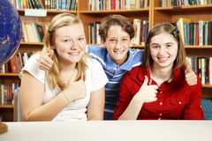 Thumbs Up for Education. Three school kids in the library, giving thumbs up for education Royalty Free Stock Image