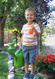 Thumbs Up Gardening. Cute little preschool aged boy giving thumbs up after watering in a garden Stock Image