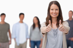 Thumbs up given by smiling woman with friends behind her Royalty Free Stock Images