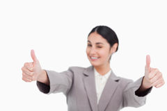Thumbs up given by smiling young businesswoman Royalty Free Stock Images