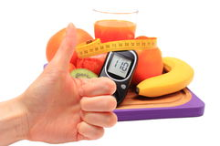 Thumbs up, glucometer and healthy ingredients with tape measure Stock Photos